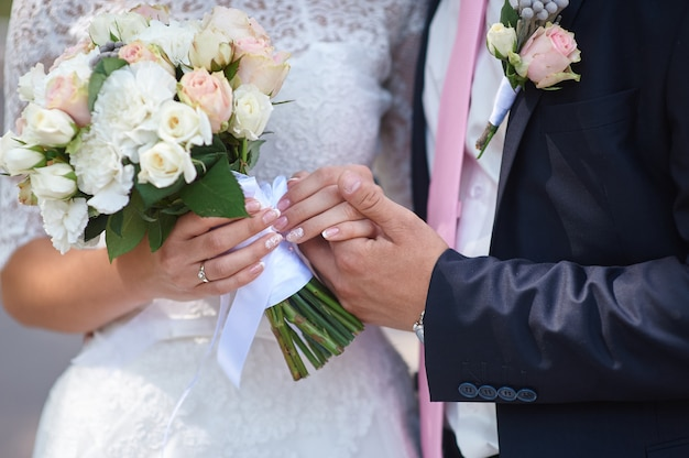 Groom holds his brides hand and a wedding bouquet Premium Photo