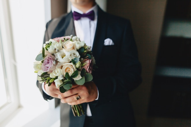 The groom holds a wedding bouquet in his hands Free Photo