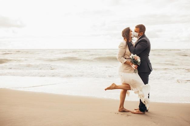 シックなスーツの新郎とビーチを歩いているウェディングドレスの美しい花嫁。防護マスクで新婚キス。トーン Premium写真
