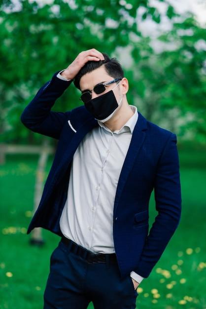 屋外の公園での結婚式の前に医療マスクで新郎します。コロナウイルス感染の検疫とパンデミックの期間中の結婚式 Premium写真
