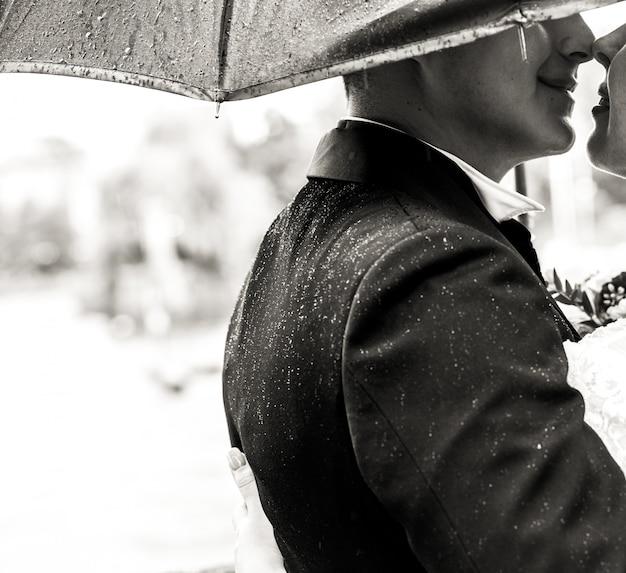 Groom kisses bride's tender standing under umbrella in the rain Free Photo