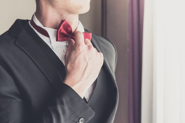 Groom looking in mirror and touching bowtie Premium Photo