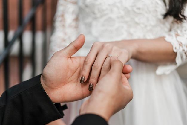 Sposo che mette l'anello nuziale sul dito della sposa Foto Gratuite