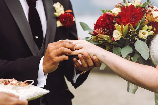 Groom puts wedding ring on bride's finger Free Photo