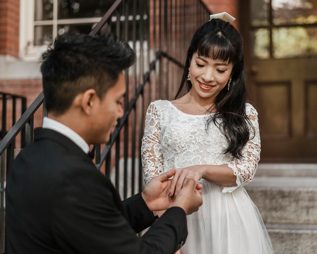 Sposo che mette la fede nuziale sul dito della sposa Foto Gratuite