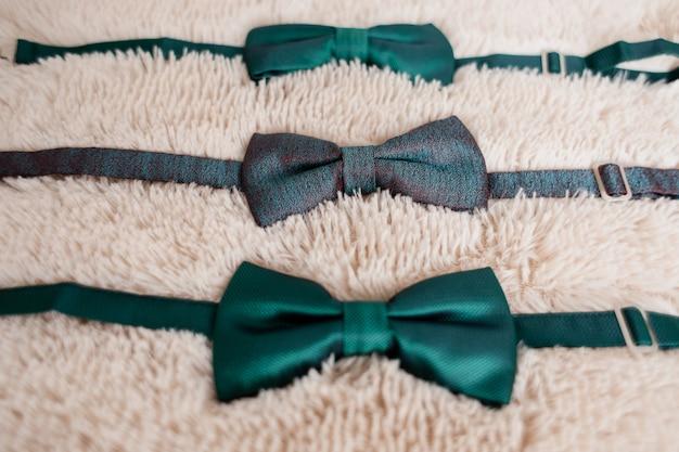 Papillon verdi da sposo e da uomo migliori sul tappeto bianco Foto Gratuite