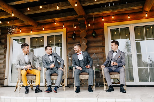 The groom's friends sit on the terrace of the house and drink whiskey Premium Photo