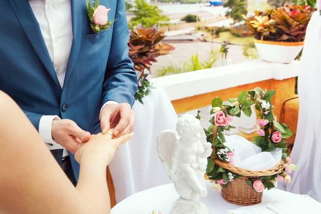 新郎の手が花嫁の指に結婚指輪を置く Premium写真
