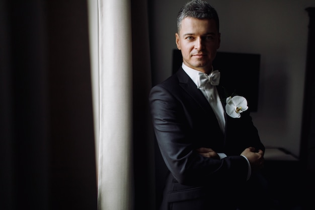 Groom's morning. handsome man in black tuxedo with white orchid Free Photo