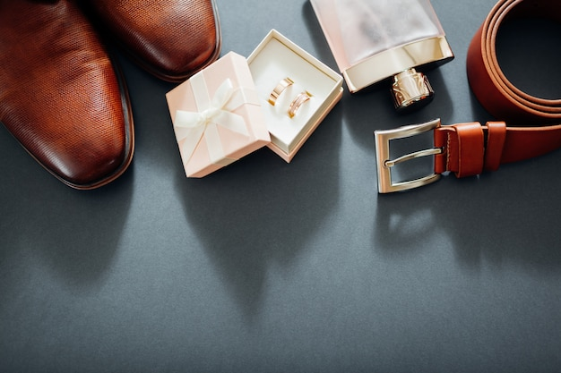 Groom's wedding day accessories. brown leather shoes, belt, perfume, golden rings. male fashion Premium Photo