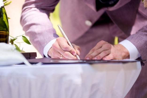 Groom signing marriage license. signature ceremony. wedding tradition. Premium Photo