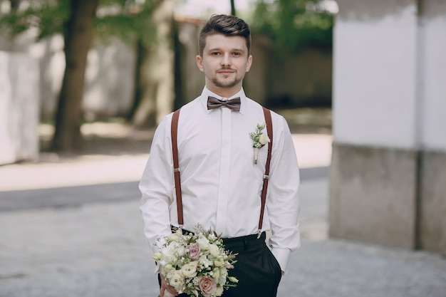 Groom in suspenders with a bouquet Free Photo