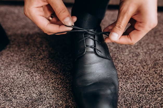 Groom ties laces on his shoes sitting on a sofa Free Photo