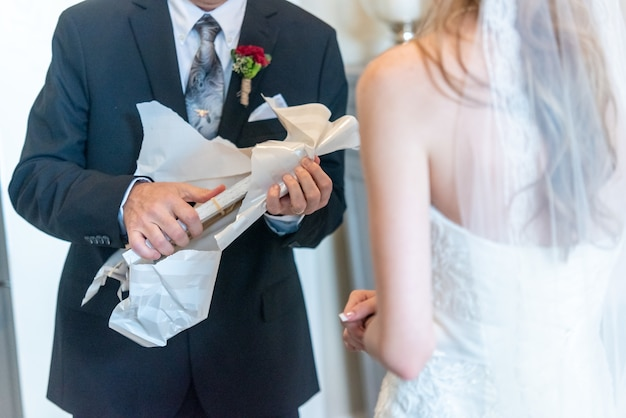 Groom unwrapping the gift on a wedding day Free Photo