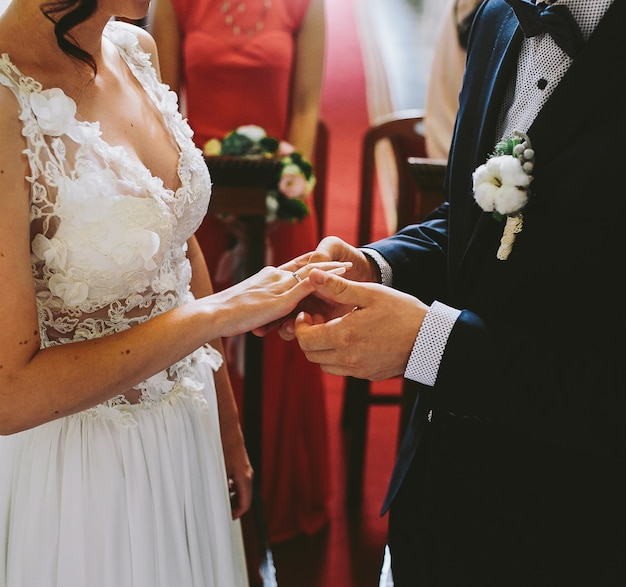 新郎は教会の花嫁の指に指輪をつけています 無料写真