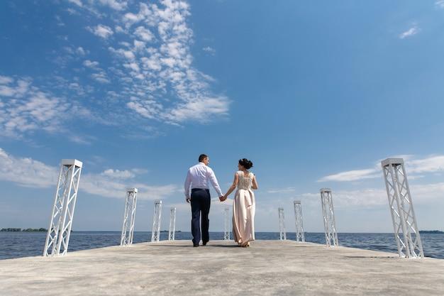 感情的な花嫁と花groomの晴れた日に.wedding日橋の上を歩きます。男と女は穏やかにお互いを見て、屋外で手を繋いでいます。デートのロマンチックな瞬間 Premium写真