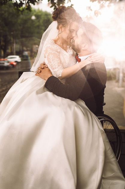 Groom on wheelchair holds bride on his knees sitting outside in the park Free Photo