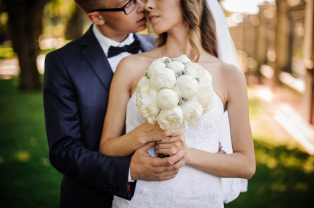 Groom with glasses is going to kiss the charming bride in a white dress Premium Photo