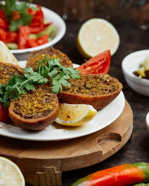 Ground meat in fried bread with slices of lemon and tomato Free Photo