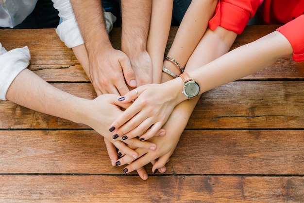 Group of adult friends putting hands together on table Free Photo