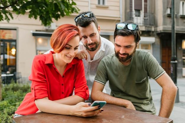 Group of adult friends using smartphone on street together Free Photo