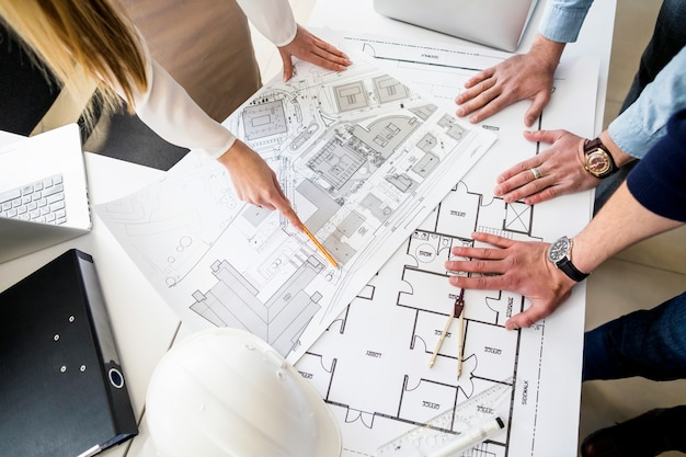 Group of architects analyzing blueprint on table Free Photo