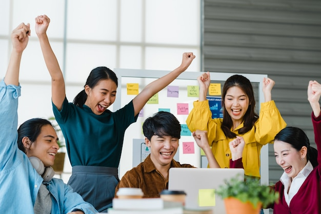 Group of asia young creative people in smart casual wear discussing business celebrate giving five after dealing feeling happy and signing contract or agreement in office. coworker teamwork concept. Free Photo