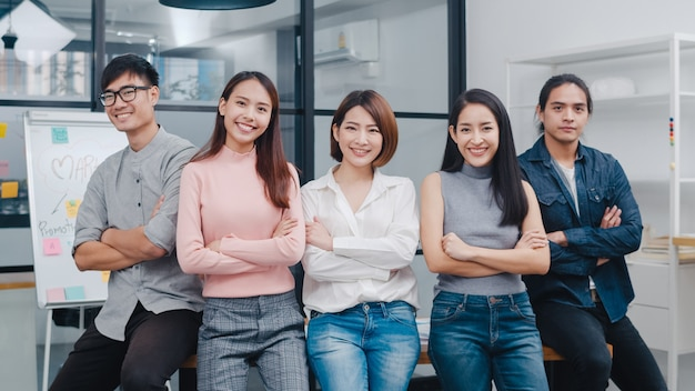 Group of asia young creative people in smart casual wear smiling and arms crossed in creative office workplace. Free Photo