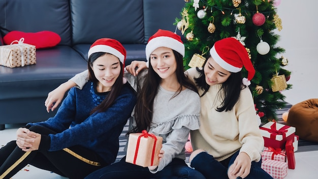 Group of asian beautiful woman holding gift boxes. smiling face in room with christmas tree decoration Premium Photo