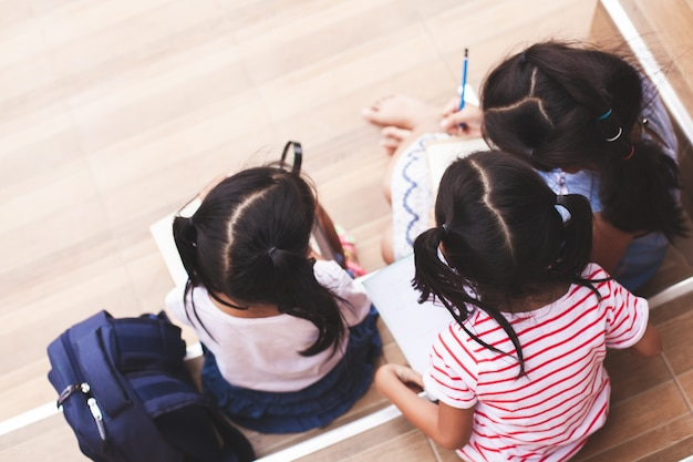 Group of asian children reading a book and writing a notebook together Premium Photo