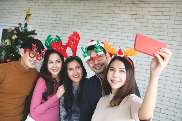 Group of asian friends taking selfie with friend together by smartphone at home during chrismas eve party or new year celebrate party. happy winter xmas and happy new year party concept Premium Photo