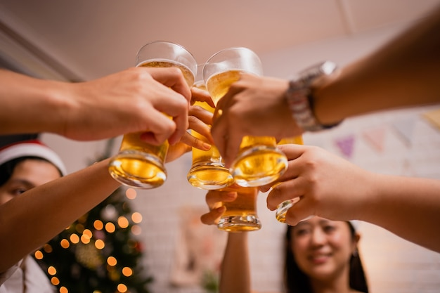 Group of asian people clink glasses at a party christmas at home. they are very happy and fun. Premium Photo