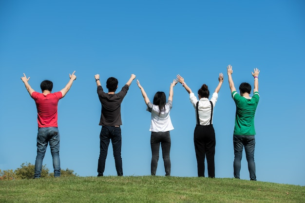Group of asian student raising hands up in park at campus in university. Premium Photo