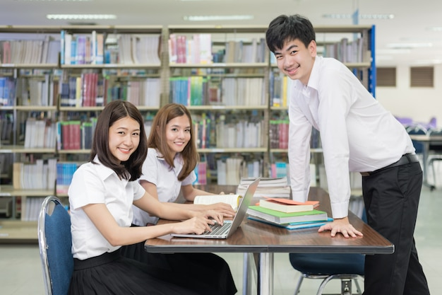 Group of asian students in uniform studying together at library. Premium Photo