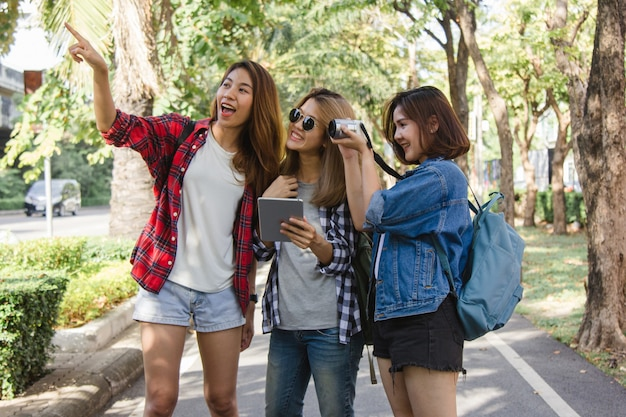 Group of asian women using camera to make photo while traveling at park in urban city in bangkok Free Photo