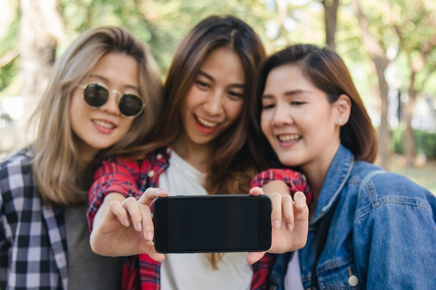 Group of asian women using smartphone taking selfie while traveling at park in urban city in bangkok Free Photo