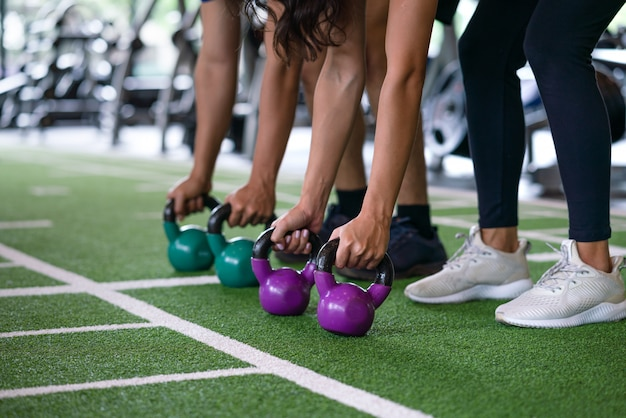 Group of athletic young man and woman workout training and exercise with kettlebell weight at fitness gym sport club Premium Photo