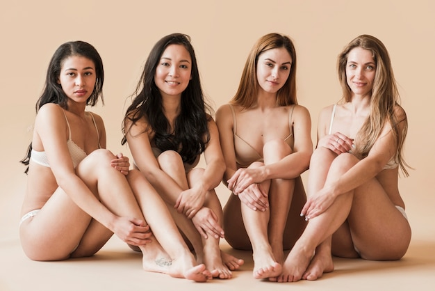 Group of attractive young women in underwear sitting in studio Free Photo