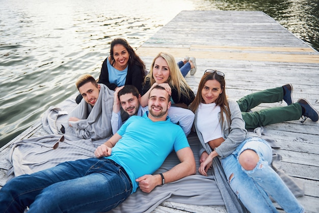 Group of beautiful young people on the pier, friends satisfaction creates emotional life. Free Photo