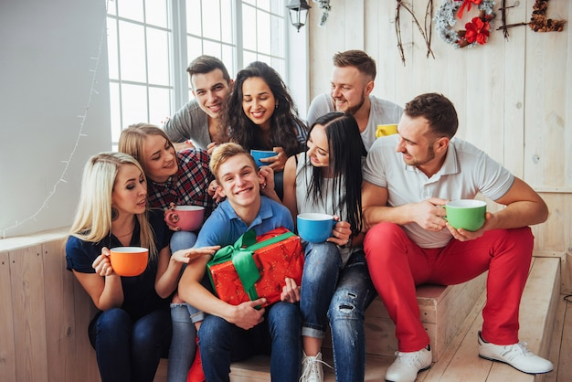 Group of best friends at party. smiling and cheerful people sitting on the stairs  a cup  coffee  greet the birthday,  great gift Premium Photo