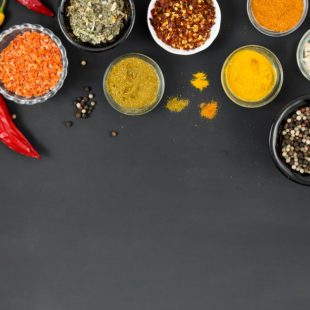Group of bowls full of spices on black background Free Photo