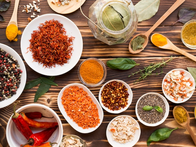 Group of bowls full of spices on wooden background Free Photo
