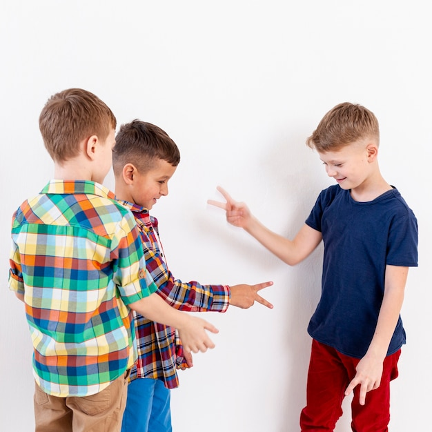 Group of boys playing rock scissors paper game Free Photo