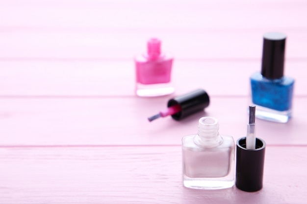 Group of bright nail polishes on pink Premium Photo