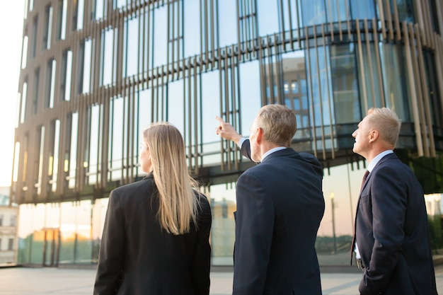 Group of business partners in formal suits pointing at office building, meeting outdoors, discussing real property. back view. commercial real estate concept Free Photo