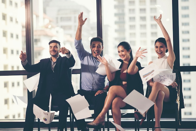 Group of business people celebrating by throwing their business papers in the air Premium Photo