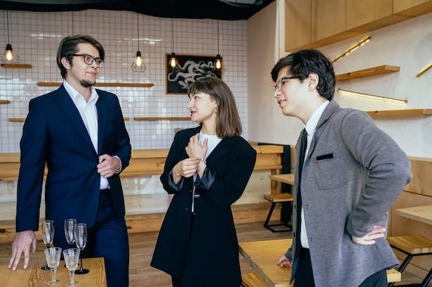 Gruppo di uomini d'affari in una riunione in piedi raggruppati in un ufficio Foto Gratuite