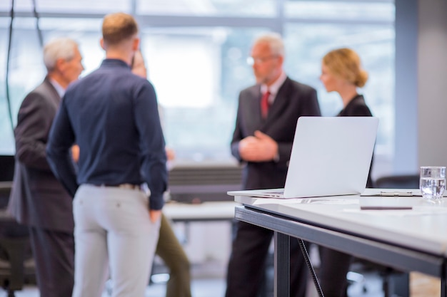 Group of business people standing in front of laptop on table Free Photo