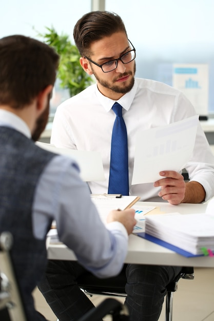 Group of businessmen with financial graph and silver pen in arm solve and discuss problem with colleague portrait. situation examination at board council sale adviser job stock exchange market profit Premium Photo