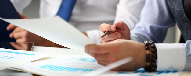 Group of businessmen with financial graph and silver pen Premium Photo